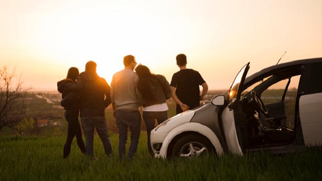 friends going on a roadtrip watching the sun set
