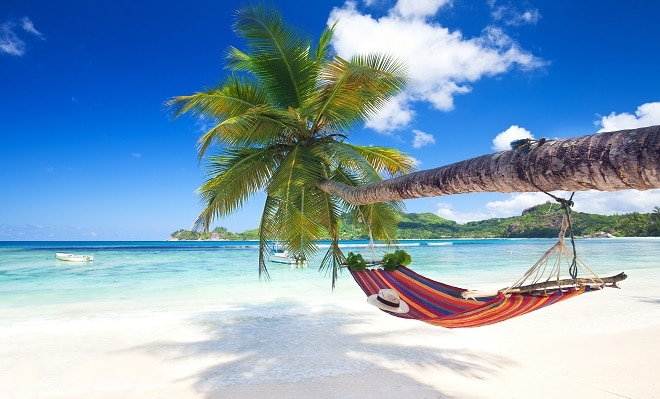 Thompson Holidays Seychelles beach white sand blue skies ocean and a red hammock hanging from a palm tree