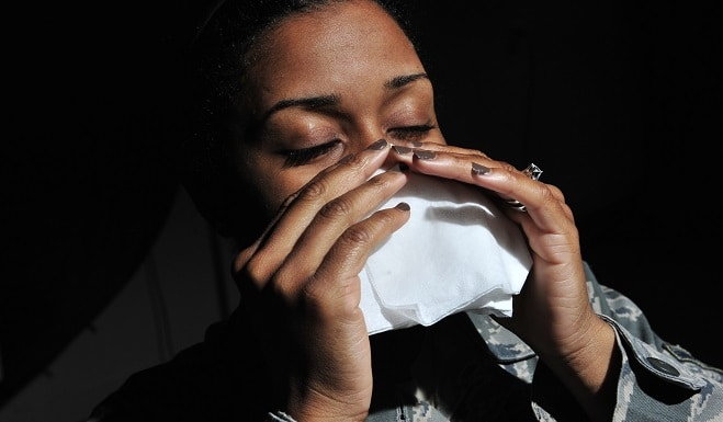 woman sneezing into a tissue with a black background