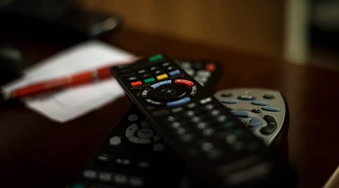 remote on wooden table in front of tv