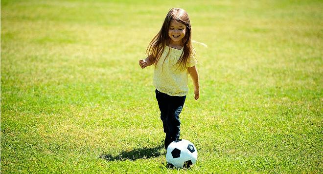lockdown little girl kicking a soccer ball outside on green grass