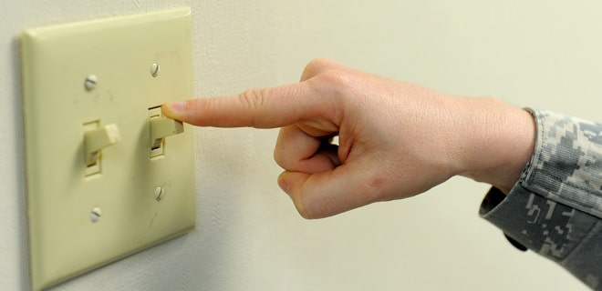 clean light switch hand turning off light switch on a white wall