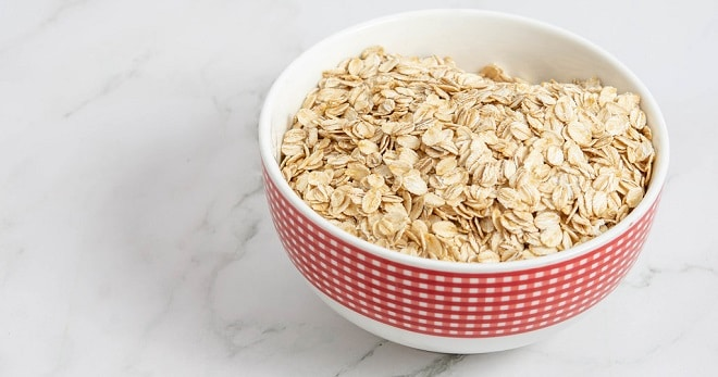oatmeal in the red bowl on a marble counter