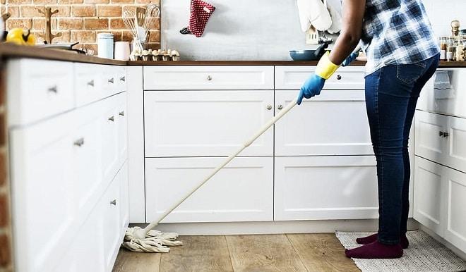 women clean kitchen floor with mop lockdown