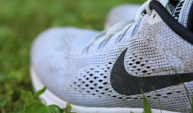 lockdown walking grey nike sneakers on green grass