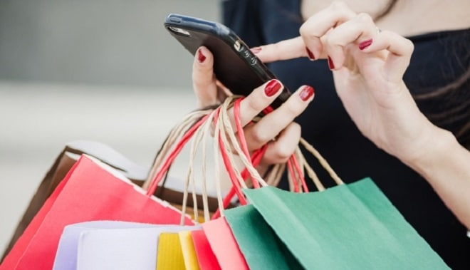 woman-with-shopping-bags-holding-smartphone