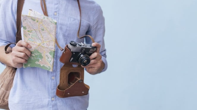 yourist holding a map and camera