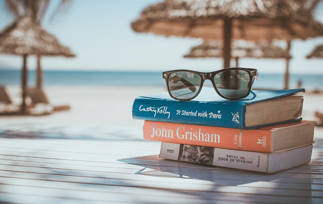 pile of books on a tacle with glasses on top and beach in the background